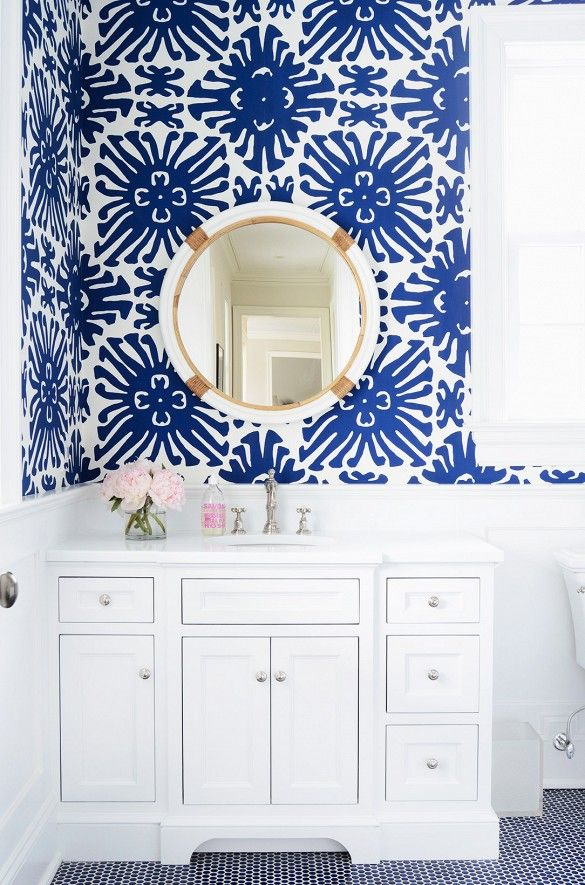 Bold, oversized royal blue starburst adds excitement to the small white bathroom